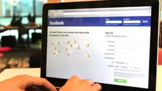 A laptop displaying the Facebook homepage.