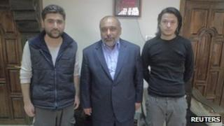 Turkish journalists Adem Ozkose (L) and cameraman Hamit Coskun (R) pose with the President of the Foundation for Human Rights and Freedoms and Humanitarian Relief Fehmi Bulent Yildirim in Damascus, in this handout picture released by IHH on May 7, 2012