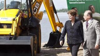 President Dilma Rousseff and the governor of Rio Grande do Sul state, Tarso Genro walking by a backhoe loader