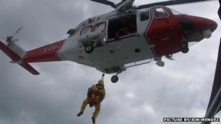 Winch man Simon O'Mahony (orange) and BBC reporter Joe Lumley (yellow) being winched