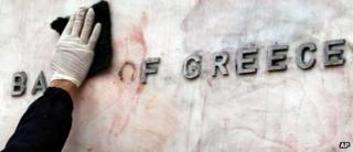 A worker cleaning a sign for the Bank of Greece