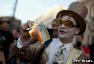 Protester burns a euro note