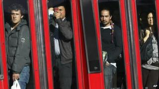 Commuters look at the site of the bomb blast in Bogota as they go past in a bus on 15 May 2012