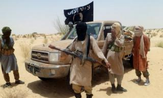 Ansar Dine men stand next to a car