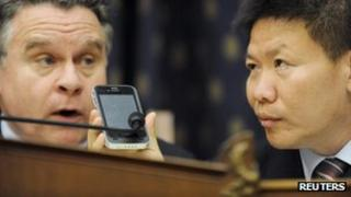 """Bob Fu (R) helps U.S. Representative Chris Smith (R-NJ) speak by phone with blind Chinese dissident Chen Guangcheng in the middle of a Congressional-Executive Commission on China hearing on Chen""""s case, on Capitol Hill in Washington May 3, 2012."""