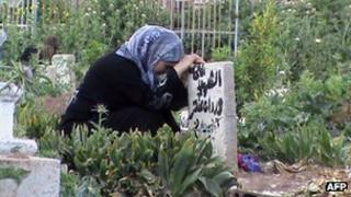 A Syrian woman mourns the death of a relative at a grave in the city of Rastan