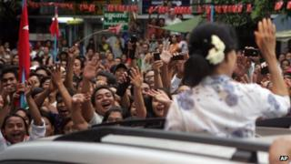 A crowd of supporters surround a car carrying pro-democracy leader Aung Sung Suu Kyi in Rangoon, Burma