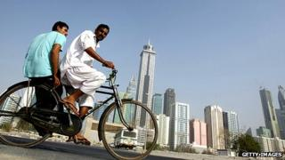 Foreign workers cycle past Dubai skyscrapers