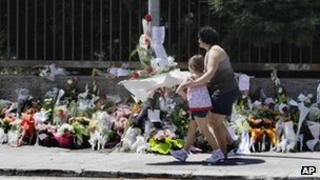 People leave flowers at the site of Saturday's school bombing in Brindisi