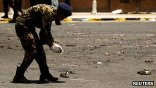 Soldier collecting evidence after the 21 May 2012 suicide bombing at a military parade in the Yemeni capital Sanaa