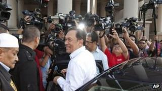 Malaysian opposition leader Anwar Ibrahim surrounded by media as he arrives to face charges in Kuala Lumpur on 22 May 2012