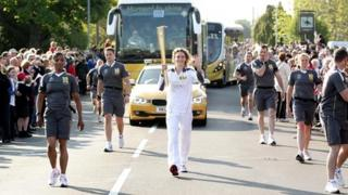 Olympic gold medalist Amy Williams carries the torch on day four