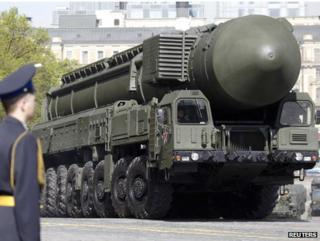 A Russian soldier stands guard as a Topol-M ICBM is driven on to Red Square during a parade rehearsal, 6 May
