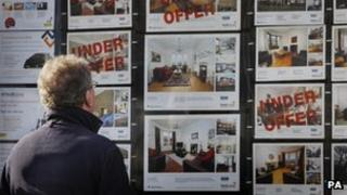 Man looking at estate agent's window