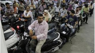 Indian motorists wait their turn at a fuel pump after the Indian government decided to hike prices of petrol by 11.5 percent, in Ahmedabad, India, Wednesday, May 23, 2012