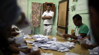 An Egyptian policeman watches as officials counting the vote after they polls are closed in Cairo May 24, 2012.