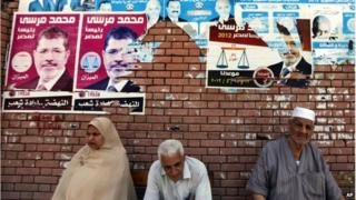 Egyptians sit beneath campaign posters supporting the Muslim Brotherhood outside a polling centre in Alexandria, Egypt