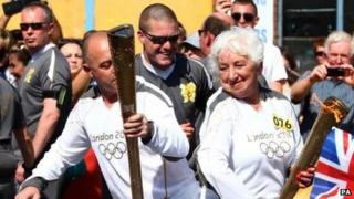 Marlene Barnett passes the Olympic flame on in the relay through Newport