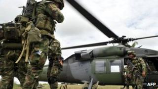 Airborne soldiers board a helicopter in Guerima, in the eastern province of Vichada, eastern plains of Colombia, on March 9, 2011