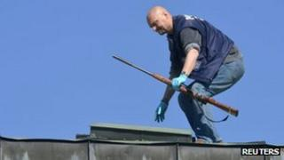 A police officer finds the rifle used by a gunman from a rooftop in a Finnish town centre in Hyvinkaa May 26, 2012