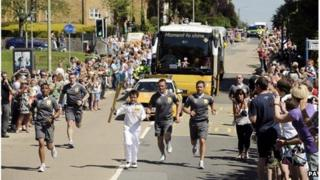 Torchbearer William Watkins carrying the flame on the leg between Bryncethin and Pyle