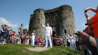 Torchbearer Peter Hale holds the Olympic torch high outside Kidwelly Castle