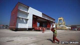 Section of the aircraft carrier being loaded onto a barge at Cammell Laird