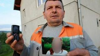 A neighbour holds the picture he took of a German girl allegedly enslaved by a couple in Bosnia
