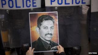 A supporter of Abdulhadi al-Khawaja holds up his picture in front of a line of riot police during a rally in Bahrain's capital Manama in April.