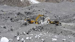 Pakistani military personnel use heavy machinery as they search for avalanche victims during an ongoing operation at Gayari camp near the Siachen glacier on April 18, 2012.