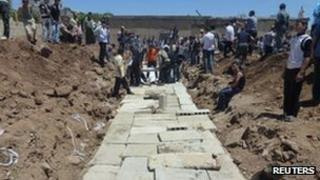 Concrete slabs are seen over a mass burial site for those killed in Friday's attacks in Houla