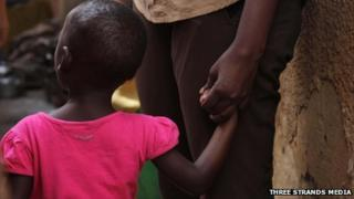 A child in Uganda holding an adult's hand