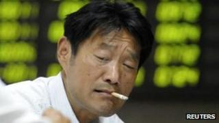 An investor smokes in front of an electronic board showing stock information at a brokerage house in Nanjing, Jiangsu, 9 May 2012