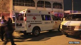 Members of the Red Cross stand beside their ambulances outside a drug rehabilitation clinic which was attacked by gunmen in the outskirts of Torreon