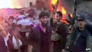 Screengrab of online video purportedly showing Syrian rebels brandishing their weapons in front of a burning tank (2 June 2012)
