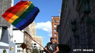 A man waves a rainbow flag outside the 9th Circuit Court in San Francisco, California