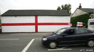 A car with flags drives past a giant flag of St George that has been painted on the side of a house ahead of the 2006 World Cup.