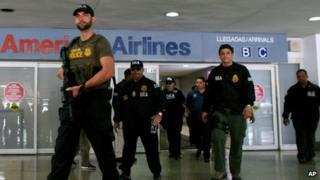 DEA agents escort a handcuffed suspect in San Juan, Puerto Rico, 6 June 2012