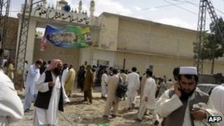 People gather outside a madrassa where a blast killed 15 people