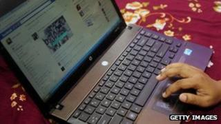 A Bangladeshi woman logs onto social networking website Facebook on her laptop in Dhaka