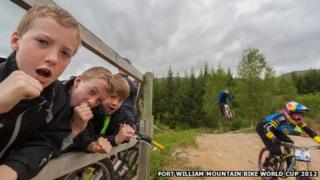 Boys cheering on mountain bike riders