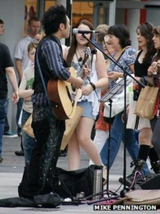 A busker performing in Liverpool's Church Street