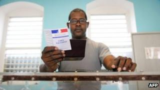 A scrutineer checks the electoral card of an overseas voter before the vote in the first round of the 2012 French parliamentary elections