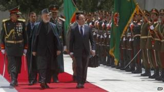 Afghan President Hamid Karzai, centre, and French President Francois Hollande, right, inspect the honour guards in Kabul, Afghanistan
