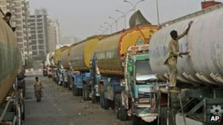 A Pakistani man, right, paints an oil tanker, which was used to transport NATO fuel supplies to Afghanistan