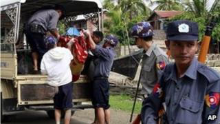 Burmese policemen carry an unidentified body to a truck at a village in Sittwe, capital of Rakhine state in western Burma on 11 June, 2012