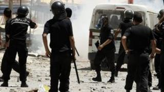 Riot police chase after protesters in the Ettadhamen district of the capital, Tunis