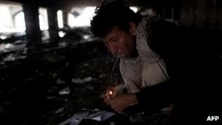 A man smokes heroin under a bridge in Kabul, Afghanistan 25 April 2012