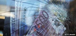 A broken window in front of a poster featuring Euro banknotes