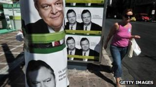 A woman walks by pre-election posters of Greek socialist party leader Evangelos Venizelos